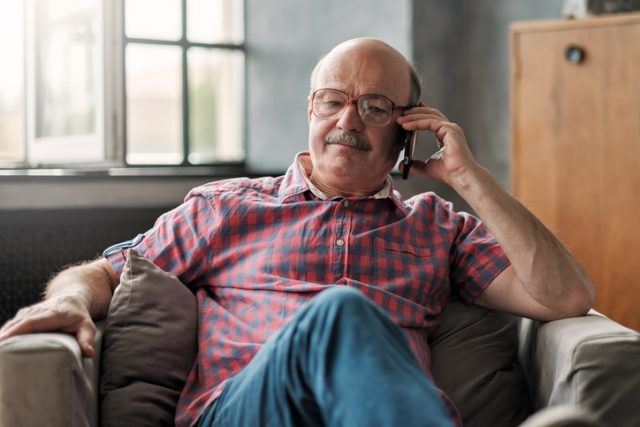 A man in his late 40s calling his family from abroad