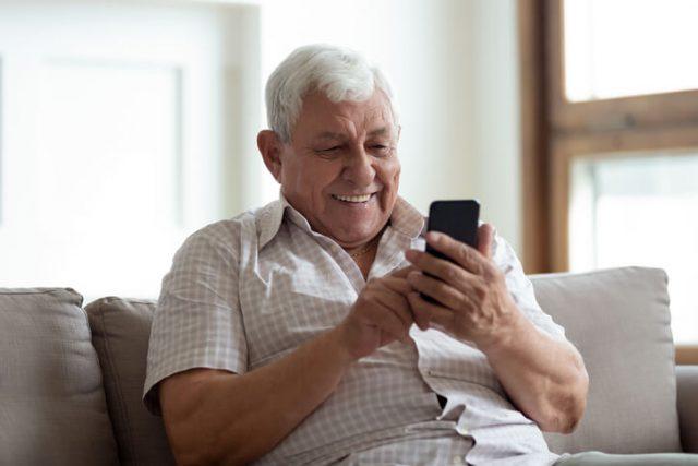 A man in his fifties is sending an international text message