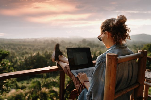 A young women using her laptop in her hotel balcony during her vacation trip abroad