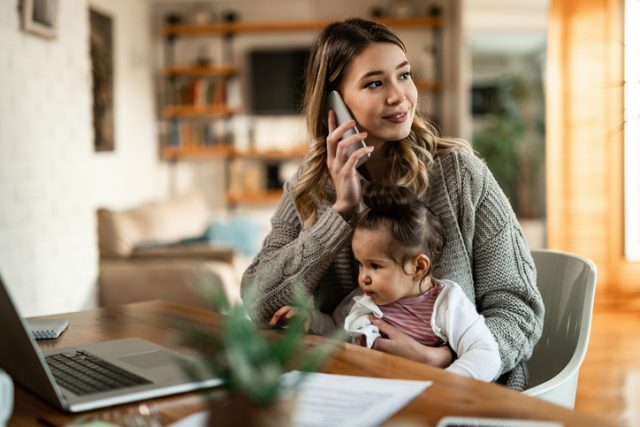 A young women is making an international call while holding her baby