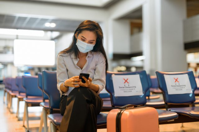 A young lady is waiting at the airport for her flight while wearing mask