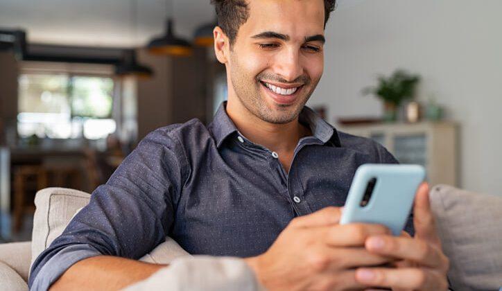 A young guy sending a text message through his phone