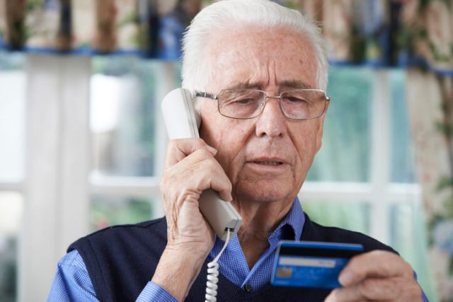 A gray hair old man sending telling his credit card details over the phone
