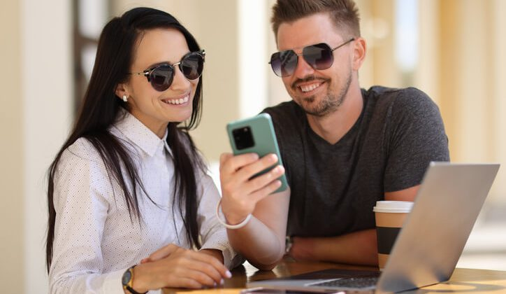 A young couple sending text message through android app