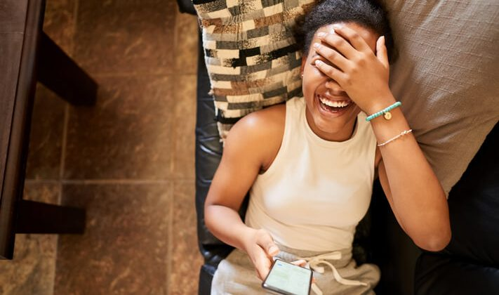 A young girl laughing while seeing a funny text message joke