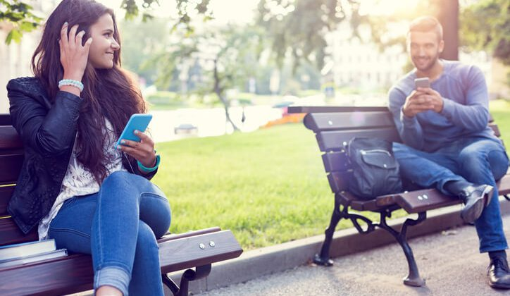 A Girl sitting in a park flirting over text with the boy sitting next to her